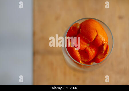Discarded orange peel in a wine glass - Stock Image