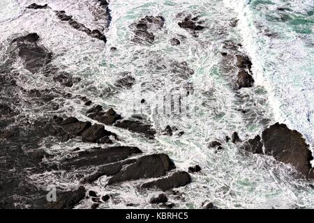 View from above of surf breaking over rocks. - Stock Image
