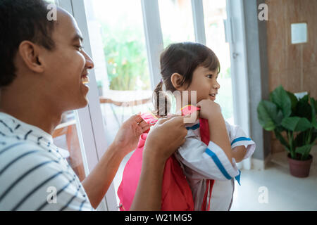 father help her toddler kid preparing for school in the morning. young kindergarten student wearing school uniform - Stock Image