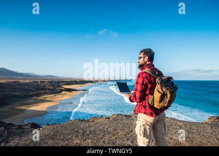Hipster people using outdoor cimputer laptop with internet connection for work or to communicate at home - traveler with backpack and alternative trav - Stock Image