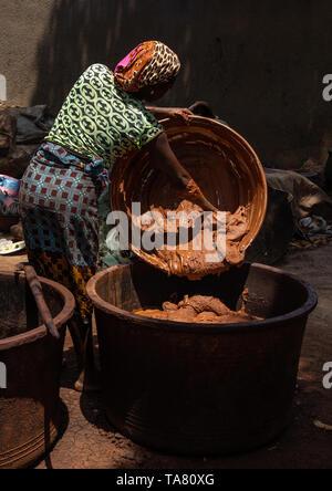 Senufo woman prepairing shea butter in a traditional karité factory, Savanes district, Tcheregnimin, Ivory Coast - Stock Image