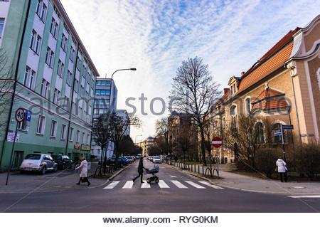 Poznan, Poland - March 1, 2019: Street with woman with baby buggy walking on a zebra crossing in the city center. - Stock Image