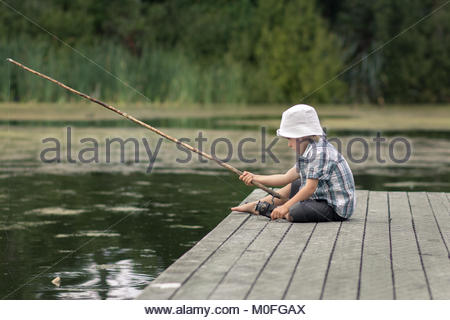 Little boy with old-fashioned fishing rod on a wooden pier - Stock Image