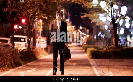 Businessman with briefcase standing on street against night view of city - Stock Image
