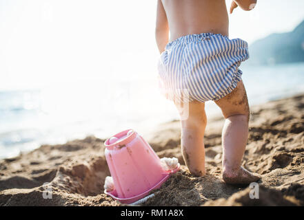 A midsection of small toddler girl with shorts playing on sand beach on holiday. - Stock Image