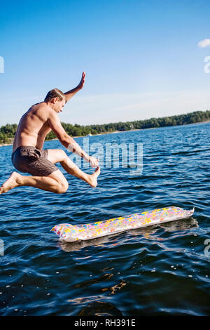 Man jumping in water - Stock Image