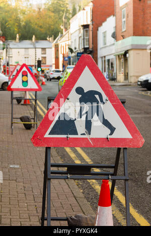 Temporary road works signs and traffic lights controlling vehicle access during highway repairs on a typical British urban street - Stock Image