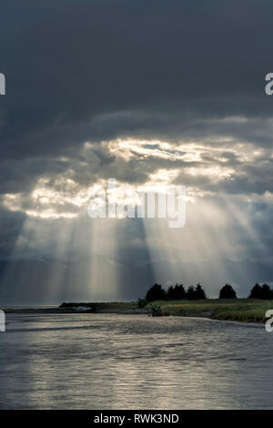 Sun rays shining down over Eagle River and Eagle Beach, Chilkat Mountains, Southeast Alaska; Alaska, United States of America - Stock Image