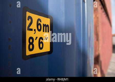 A line up of two containers with a 2.6m and 8'6' height sticker in the foreground and with a blurred background - Stock Image