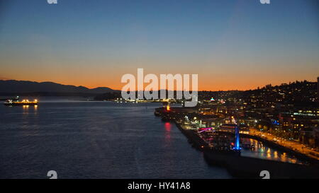 Illuminated City By River Against Sky At Sunset - Stock Image