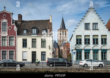 Architectural styles of waterfront buildings, with church tower in the background, Bruges, West Flanders, Belgium. - Stock Image