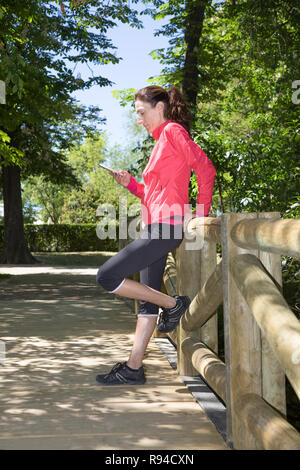 sporty adult woman with pink sweater, watching mobile smartphone leaning in wooden railing of footbridge, in park of Retiro, in Madrid, Spain. Vertica - Stock Image