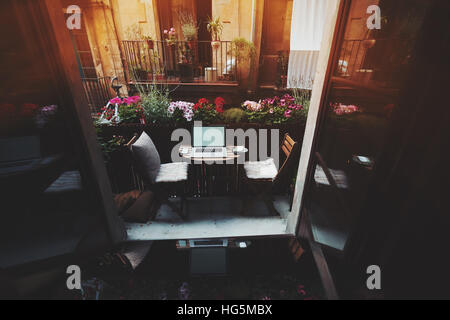 Small cozy beautiful workspace on balcony with laptop, mouse, smartphone, chairs and flowers around on sunny summer - Stock Image
