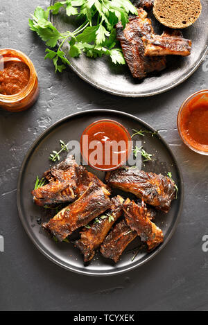 Barbecue spare ribs on plate over black stone background. Tasty bbq meat. Top view, flat lay - Stock Image