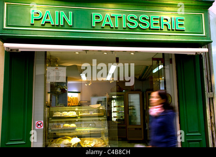Arles; Bouches du Rhone, France; Young woman walking in front of a brightly coloured facade of a 'pain patisserie' - Stock Image