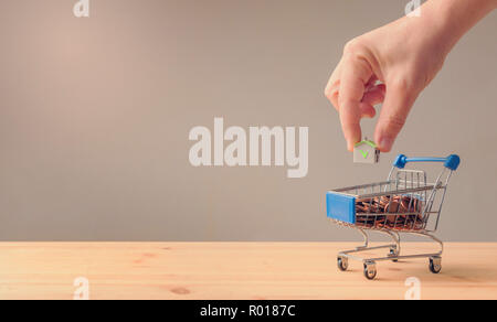 Male hand put a paper house into a cart full of coins, saving and loan or mortgage concept - Stock Image