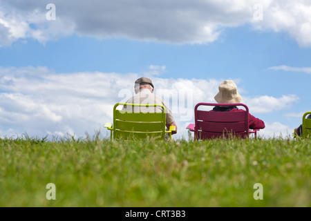 Senior couple enjoying retirement - relaxing in the park against a clear blue sky. - Stock Image