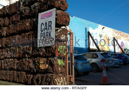 Car parking for the Custard Factory - creative use of baled crushed cars and wall murals in the Digbeth area of central Birmingham, West Midlands, UK. - Stock Image