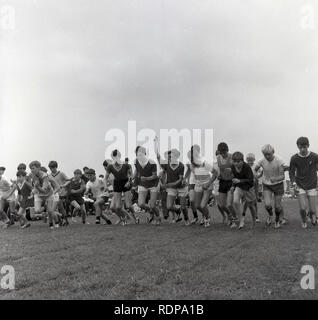 1967, school sports, the starting gun goes off and the schoolboys start the running race on a grass track, England, UK. - Stock Image