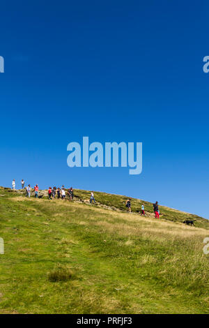 A group of young people and other walkers and their dogs on the footpath leading south from the summit of Cat Bells (451 metres) near Keswick, Cumbria - Stock Image