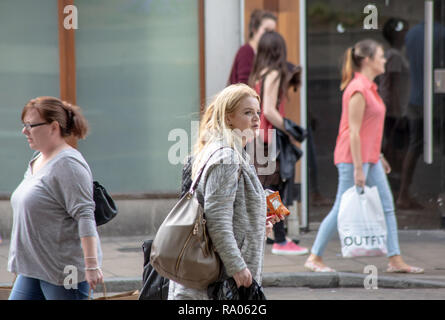 A young Woman shopper walking in the city centre in summer - Stock Image