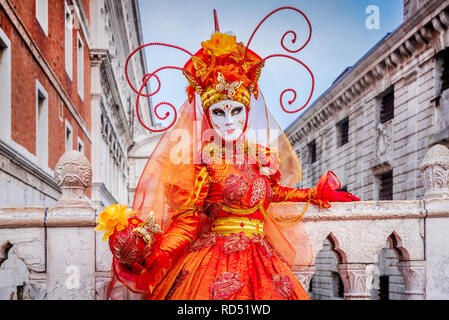 Venice, Italy, Carnival of Venice, beautiful mask at Piazza San Marco with gondolas and Grand Canal. - Stock Image
