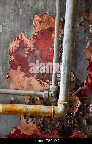 Paint peeling off plastered wall with two piped - Stock Image