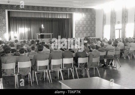1950s, school assembly, headmaster wearing robe standing on the stage addressing his pupils. England, UK. - Stock Image