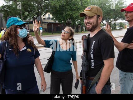 A supporter of Ilhan Omar (center) confronts anti-Muslim protesters, some opening carrying guns legally, outside an Austin, Texas, hotel where the controversial Muslim Congresswoman spoke at a city-wide iftar dinner. - Stock Image