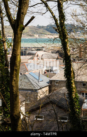 Looking between trees and over the rooftops of Padstow towards the harbour and estuary. - Stock Image