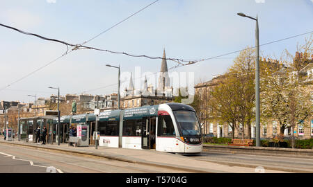 An Urbos 3 tram at the West End - Princes Street light railway station with Coates Terrace, the William Gladstone Monument and St Mary's Cathdral in t - Stock Image