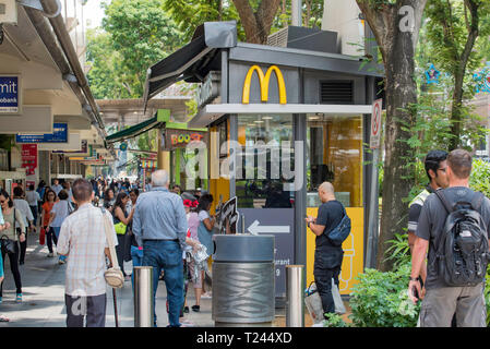 Shoppers, office workers and tourists walking along Orchard Road in central Singapore - Stock Image