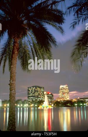 Orlando Florida Lake Eola nightly fountain light show city skyline beyond dusk - Stock Image
