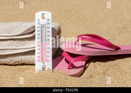 Bournemouth, UK. 26th June 2018. UK Weather, a heatwave in June. Sandy beach in Bournemouth with towels and flip flops and thermometer to check the temperature. Credit: Thomas Faull / Alamy Live News - Stock Image