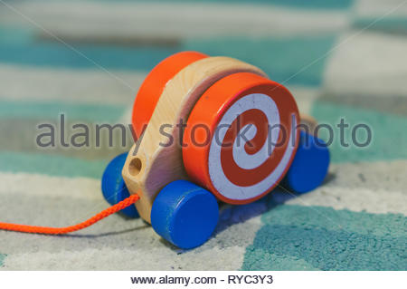 Headless wooden toy snail with red rope on a carpet in soft focus. - Stock Image