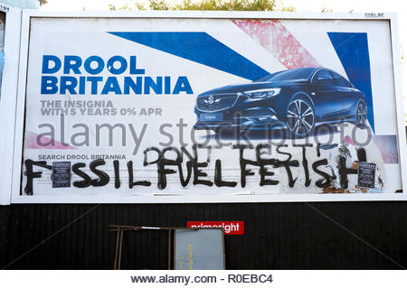 Car advert billboard defaced with environmental graffiti relating to fossil fuel. Bristol, UK. - Stock Image