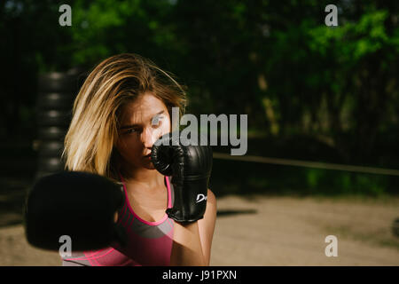 Confident girl training boxe  in a open public gym, dramatic light with lot of contrast to emphasize the model - Stock Image