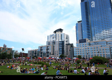 People resting on a lawn next to Smorgasburg in Williamsburg, Brooklyn on JULY 8th, 2017 in New York, USA. (Photo by Wojciech Migda) - Stock Image