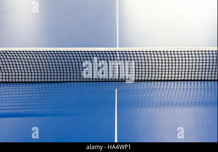 Horizontal table tennis net in black mesh dividing a blue colored ping pong table. Copy space area for sports designs. - Stock Image