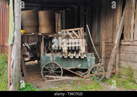 Old handcart loaded with various farm and garden detritus along with old implements in a wooden leanto shed with round bales in the barn behind.Purbec - Stock Image