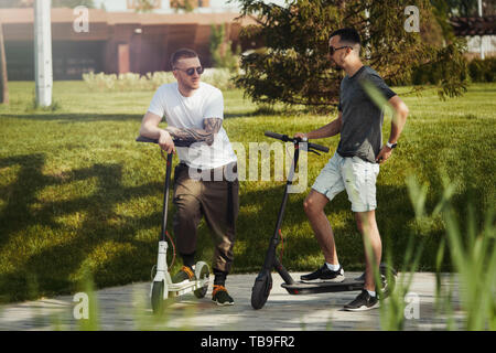 Two men talking next to white and black electric kick scooters at beautiful park landscape. Men is on foreground, modern building and park is on backg - Stock Image