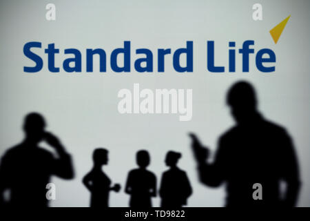 The Standard Life logo is seen on an LED screen in the background while a silhouetted person uses a smartphone in the foreground (Editorial use only) - Stock Image