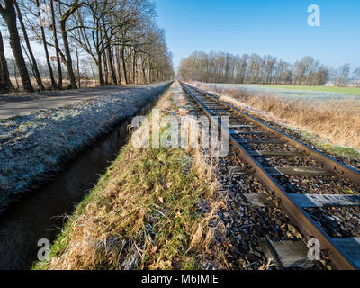 Railroad tracks of the OHE,  Osthannoversche Eisenbahnen, winter day, rural road, railway network, Lachtehausen, - Stock Image
