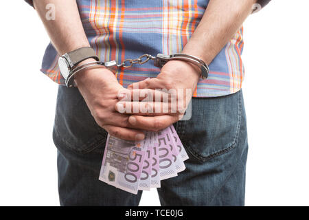 Corrupted man holding bribe money behind back with handcuffed hands closeup isolated on white studio background - Stock Image