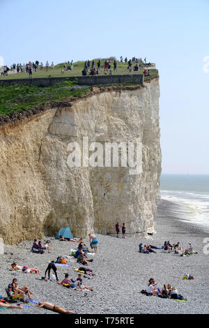Tourists risking their lives to get selfies on 400 foot crumbling chalk cliffs, Birling Gap, East Sussex, UK - Stock Image