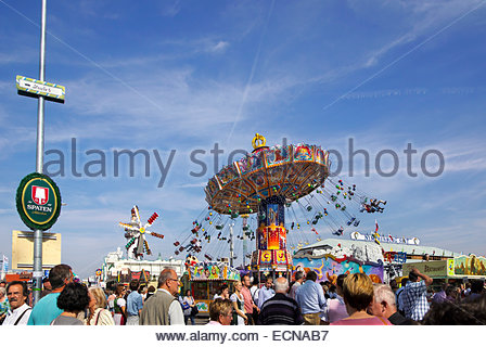 Visitors to Oktoberfest in Munich, Germany, mill around food booths and enjoy the rides. - Stock Image