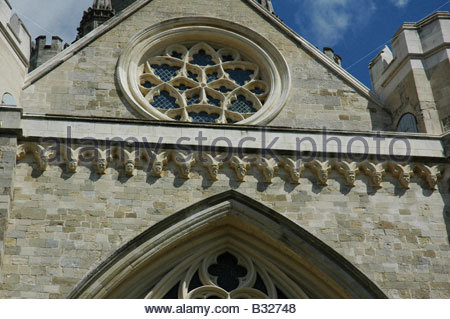 Faces carved on the corbel table on the south transept of The Cathedral Of The Holy Trinity Chichester - Stock Image