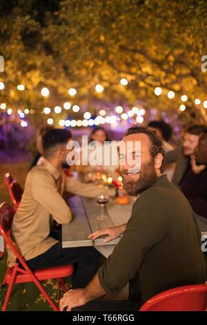 Portrait happy man enjoying dinner garden party - Stock Image