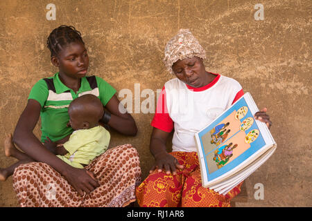 Samba village, Yako Province, Burkina Faso: Abzetta Sondo, 19, and her child suffering from acute malnutrition, get instruction from Helene Pagoundba, nutrition education committee member. - Stock Image