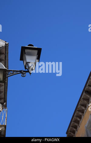 electrical retro street lantern by day, decorative and nostalgic street lamp in front of azure sky - Stock Image